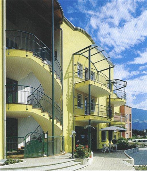 Hausfassade mit Stiegen-Balkon-Geländer und Überdachungen (Wohnanlage Rosslauf Brixen)